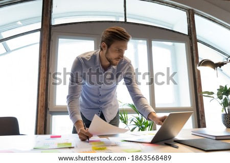Concentrated young male project manager software developer standing by desk at workplace in office involved in paperwork, checking comparing data in hardcopy and on laptop screen, making notes changes
