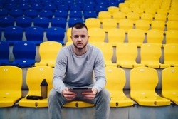 Concentrated young male trainer with stubble in sportswear looking at camera and using tablet while resting on stadium bleachers during break