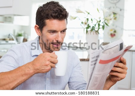 Concentrated young man drinking coffee while reading newspaper at home - stock photo