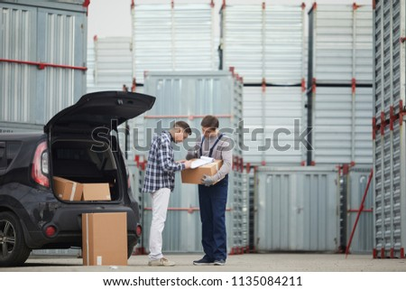 Concentrated young man in casual clothing signing contract with storage company after discussing deal: container storage worker holding box with clipboard and pointing where signature place is