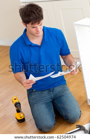 Concentrated young man reading the instructions to assemble furniture in the kitchen at home