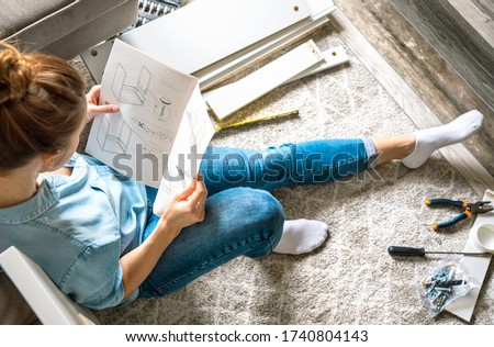 Concentrated young woman reading the instructions to assemble furniture at home in the living room ストックフォト ©