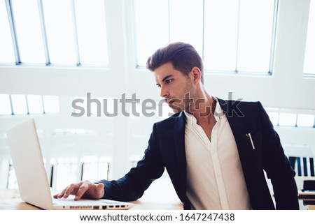 Concentrated youthful smart male freelancer focusing on laptop screen while typing and working on business project in light modern office