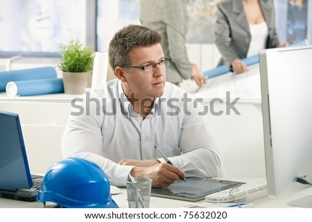 Concentrating architect at work, sitting at desk using drawing pad.?