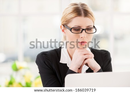 Concentrating at work. Serious mature woman in formalwear holding hands on chin and looking at laptop while sitting at her working place