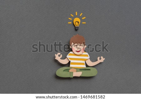 Concentrating boy  at meditation session. Relaxing guy sitting in lotus pose and meditating. Turn on bright lightbulb demonstrating new idea. Hand cut illustration from paper on white background
