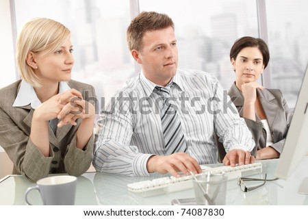 Concentrating businesspeople on meeting, looking at computer screen.?