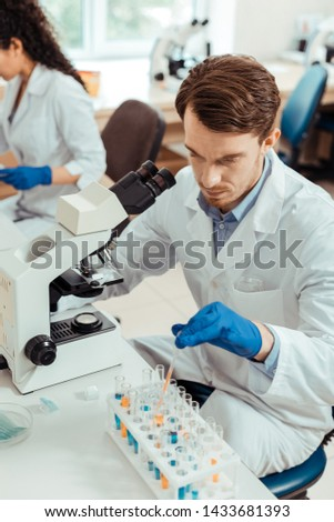 Concentrating on work. Top view of a serious bearded man sitting in front of the microscope while concentrating on work