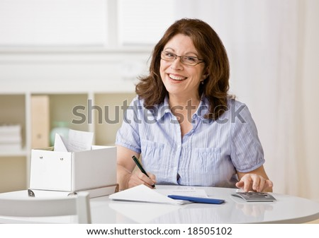 Concentrating woman using calculator to pay monthly bills