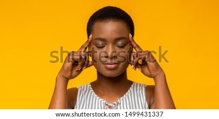 Concentration. Afro girl holding fingers on temples, thinking hard, trying to concentrate, yellow studio background ストックフォト ©