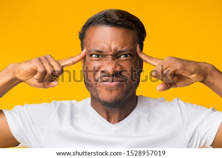 Concentration Concept. Black Man Concentrating Hard Pointing Fingers At Forehead Standing In Studio Over Yellow Background.