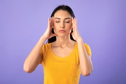 Concentration Concept. Portrait of young woman holding fingers on temples, thinking hard, trying to concentrate, isolated over purple studio background. Lady doing breathing yoga practice