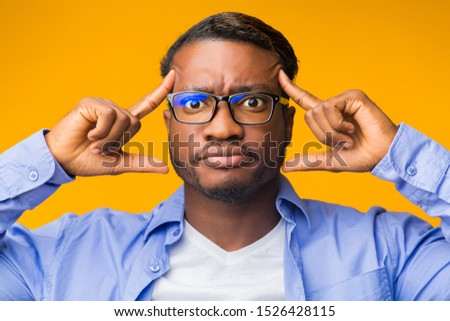 Concentration. Smart Afro Guy Concentrating Hard On An Idea Pointing Fingers At Forehead. Yellow Background, Studio Shot