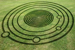 Concentric circles and spiral to make a fake crop circle in the meadow
