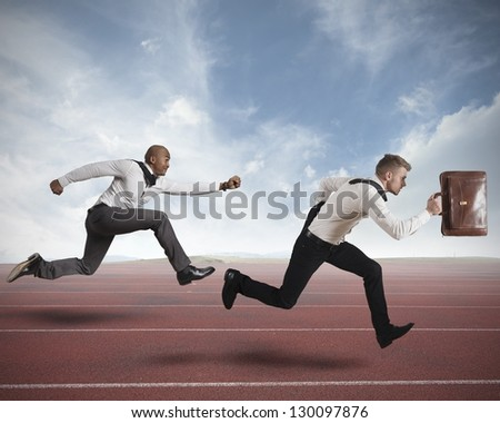 Conceot of competition with two running businessman in a track - stock photo