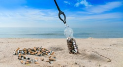 Concept about pollution collecting cigarette stubs with tongs on a beach