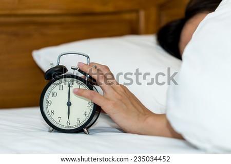 Concept alarm clock with sleep woman in comfort bed.