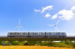 Concept application green energy in transport. Side view at metro train is which passing at overpass railroad over parkland with windmills.