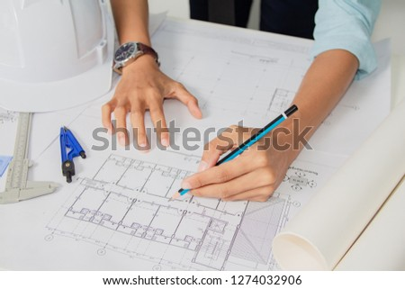 Concept architects,engineer holding pen pointing equipment architects On the desk with a blueprint in the office. .Selective Focus