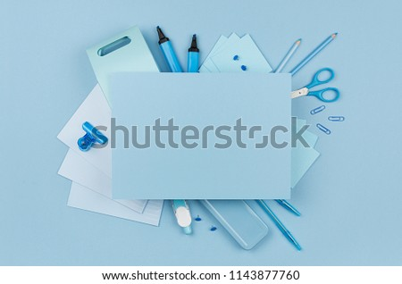 Concept art workplace for designers - blue color office accessories and blank letterhead for text on soft light blue background, top view.