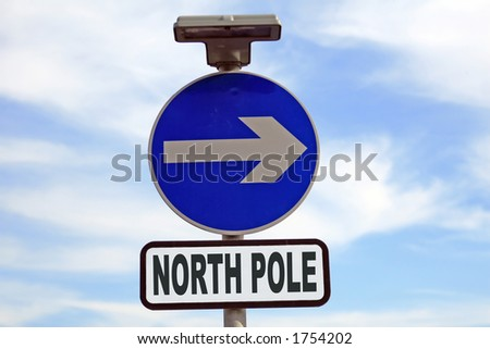 Concept: Blue sign with arrow pointing to the north pole and Christmas. - stock photo