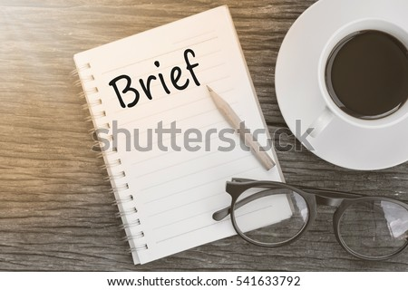 Concept Brief on notebook with glasses, pencil and coffee cup on wooden table.
