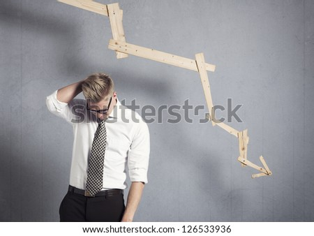 Concept: Business failure. Young worried businessman in front of business graph with negative trend, isolated on grey background.