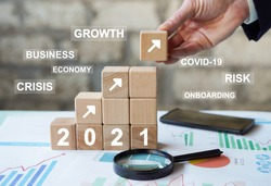 Concept business growth and risks in 2021 year covid-19. Businessman hand arranging wood block stacking with business growth in 2021 year, business onboarding, coronavirus, protect your business.