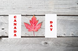 Concept Canada Day with red maple leaf on vintage wooden table