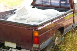 Concept : car accident on wet slippery floor. Blurred  motion photo of  old pick- up car carry overload weight of white sacks that make the car's wheels stuck and sunk on slippery muddy soil ground.