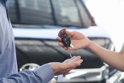Concept car rental service. Close up view hands of agent giving car key to client that rent a vehicle  in rental office.