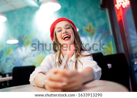 Concept caries and harm is danger to tooth enamel. Young girl eating sweet sticky stick in France cafe in red beret and glasses.