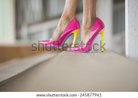 Concept close up image of woman sitting in Elegant extravagant sexy pink high heel shoes, relaxed on bench, copy space, blurred background.