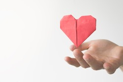Concept. Close up of a hand with an origami red paper heart floating above finger. White background.