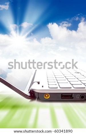 Concept - cloud computing, notebook and clouds in sky