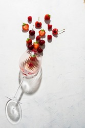 Concept composition presenting rose wine flavours of summer fruits of berries on white background