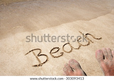 Concept, conceptual beach text handwritten in sand on a beach background with feet in an exotic island for tropical, summer, sea, ocean, calendar, travel, holiday, sunny, tourism, resort, time, relax #303093413