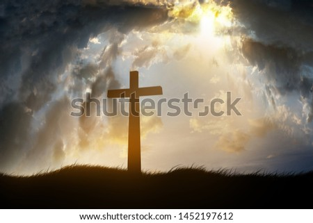 Concept conceptual black cross religion symbol silhouette in grass over sunset or sunrise sky #1452197612