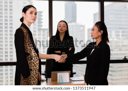 Concept Conflict at work : Two business women have conflicts in the office even though they try to handshake. By having friends as witnesses to support each other well, but without good results