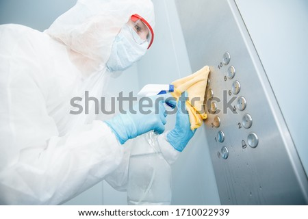 Concept coronavirus disinfection. People in hazmats making cleaning in lift apartment.