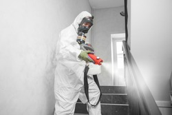 Concept coronavirus disinfection. People in hazmats making cleaning in stairwell of apartment building.
