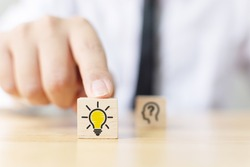 Concept creative idea and innovation. Hand choose wooden cube block with light bulb icon and blurred question mark symbol