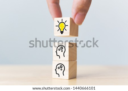 Concept creative idea and innovation. Hand picked wooden cube block with head human symbol and light bulb icon