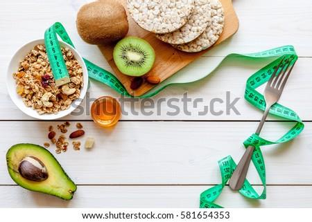 Concept diet - healthy food with muesli, honey, kiwi and cereals #581654353