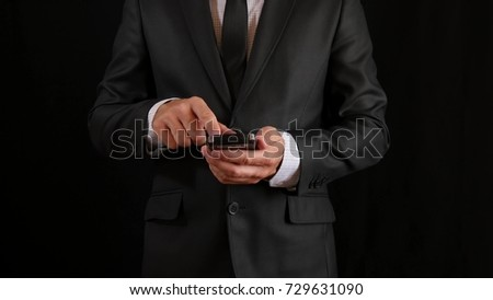 Concept, digital online life and social networks. A businessman in a business suit uses his smartphone to view his accounts. Expressive shot, a man in a dark room, holding a stylish phone  #729631090