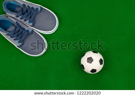 Concept encourage children to play sport, exercise for a healthy body, shoes of small baby shoes next to ball isolated on grass background. #1222202020