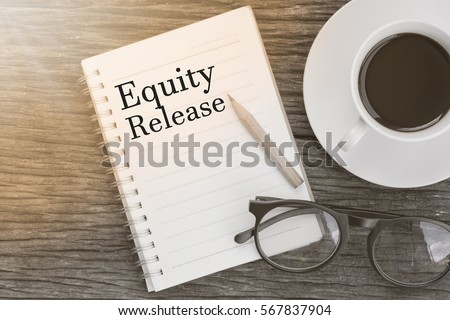 Concept Equity Release message on notebook with glasses, pencil and coffee cup on wooden table.