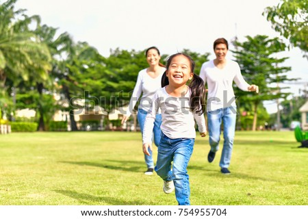 Concept Family relaxation. Parent and child go for a walk in the park. Family is doing holiday activitie. Family is running happily. Girls and parents are relaxing. Asian family playing in the garden.