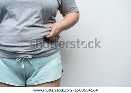 Concept fat, overweight, diet or cellulite and life and health care. hand of female touching or holding fat and waist on gray background with copy space. Fat woman hand holding excessive belly fat