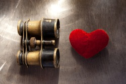 Concept Find Love. Old binoculars and heart.